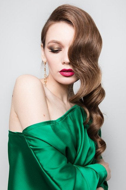 cette image représente une femme glamour avec une belle couleur brillante et un brushing wavy sur cheveux longs déporté sur le côté. Elle est présentée par Carole Créa'tifs pour sa réouverture le lundi 11 mai coiffeuse à domicile à Toulouse